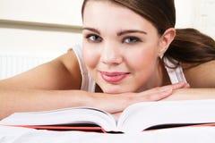 Giovane bella donna che si distende con un libro Immagini Stock Libere da Diritti