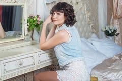 Giovane bella donna che si siede allo specchio in camera da letto con la tavola di condimento Immagine Stock Libera da Diritti