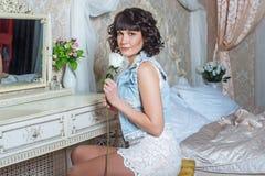 Giovane bella donna che si siede allo specchio in camera da letto con la tavola di condimento Immagini Stock Libere da Diritti