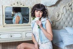 Giovane bella donna che si siede allo specchio in camera da letto con la tavola di condimento Fotografie Stock