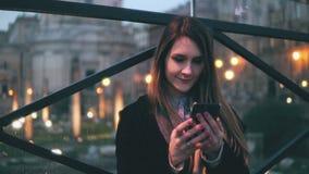 Giovane bella donna che si siede nella città allo smartphone di uso e di sera Ragazza che manda un sms con la tastiera dello sche Fotografie Stock Libere da Diritti