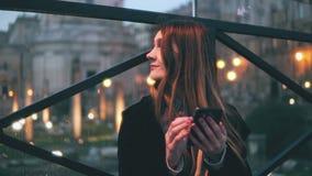 Giovane bella donna che si siede nella città allo smartphone di uso e di sera Ragazza che manda un sms con la tastiera dello sche Immagine Stock