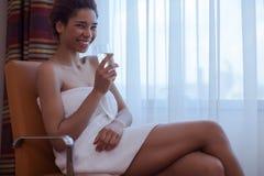 Giovane bella donna che si siede nella sedia accanto alla finestra dopo una doccia Fotografia Stock Libera da Diritti