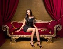 Giovane bella donna che si siede su un sofà rosso del velluto nel interi Fotografia Stock