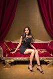 Giovane bella donna che si siede su un sofà rosso del velluto nel interi Immagini Stock
