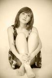 Giovane bella donna che si siede sul pavimento Fotografie Stock