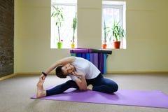 Giovane bella donna che si siede sul pavimento sulla stuoia per forma fisica e pe Fotografia Stock Libera da Diritti