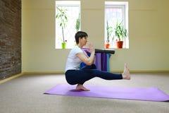 Giovane bella donna che si siede sul pavimento sulla stuoia per forma fisica e pe Fotografia Stock
