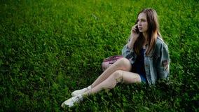 Giovane bella donna che si siede sull'erba nel parco della città di estate e che parla sul telefono cellulare archivi video