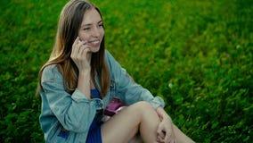 Giovane bella donna che si siede sull'erba nel parco della città di estate e che parla sul telefono cellulare stock footage