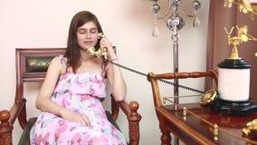 Giovane bella donna che si siede sulla sedia, parlante sul telefono d'annata, stock footage