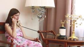 Giovane bella donna che si siede sulla sedia, parlante sul telefono d'annata, video d archivio