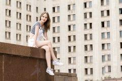 Giovane bella donna che si siede sulle scale vicino all'università Fotografie Stock
