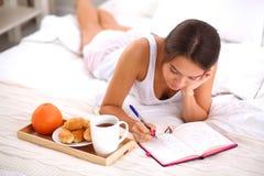 Giovane bella donna che si trova a letto scrivendo un diario Fotografie Stock Libere da Diritti