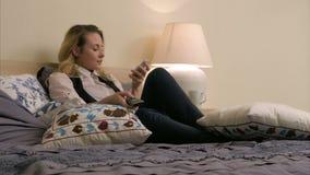 Giovane bella donna che si trova sul letto, accendente i canali televisivi e per mezzo dello smartphone a casa archivi video
