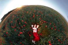 Giovane bella donna che si trova un campo del papavero Fotografia Stock