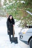Giovane bella donna che spala e che rimuove neve dalla sua automobile, Immagini Stock