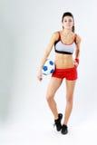Giovane bella donna che sta con il pallone da calcio Fotografie Stock Libere da Diritti