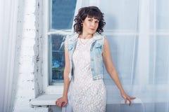 Giovane bella donna che sta contro una finestra con le tende bianche Fotografie Stock