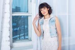 Giovane bella donna che sta contro una finestra con le tende bianche Immagine Stock