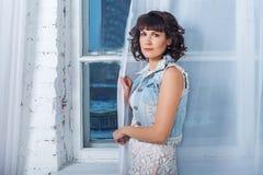 Giovane bella donna che sta contro una finestra con le tende bianche Fotografia Stock Libera da Diritti