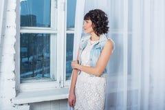 Giovane bella donna che sta contro una finestra con le tende bianche Immagini Stock Libere da Diritti