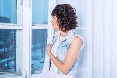 Giovane bella donna che sta e che aspetta triste guardando fuori la finestra Immagini Stock