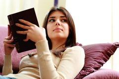 Giovane bella donna che tiene un libro e distogliere lo sguardo Fotografie Stock Libere da Diritti