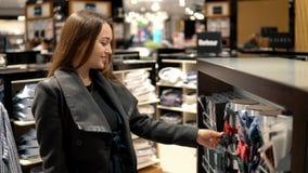 Giovane bella donna che trova una cravatta a farfalla del regalo in un supermercato del deposito archivi video