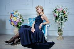 Giovane bella donna con capelli biondi lunghi in vestito blu scuro elegante che posa allo studio bianco Fotografia Stock