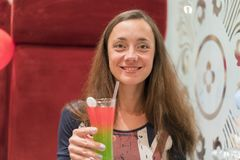Giovane bella donna con capelli lunghi in un ristorante con un cocktail a disposizione immagine stock