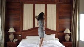 Giovane bella donna con capelli lunghi in vestito variopinto che balla, saltante e filante sul letto in camera da letto con grand archivi video