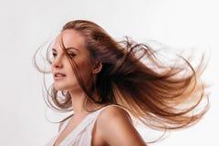 Giovane bella donna con capelli scorrenti su un fondo bianco Immagini Stock Libere da Diritti