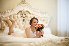 Giovane, bella donna con i fiori su un letto immagine stock