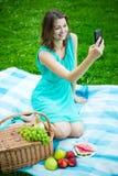 Giovane bella donna con il canestro di picnic e frutti facendo uso di astuto Fotografie Stock Libere da Diritti