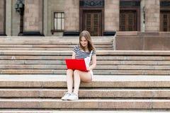 Giovane bella donna con il computer portatile che si siede sulle scale vicino all'università Fotografia Stock Libera da Diritti