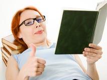 Giovane bella donna con il libro di lettura rosso dei capelli Fotografie Stock