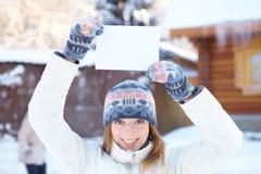 Giovane bella donna con l'insegna in bianco. Inverno. Fotografia Stock Libera da Diritti