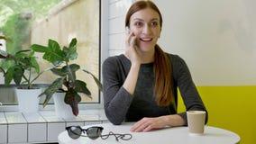 Giovane bella donna con la coda di cavallo che si siede in caffè, parlante sul telefono, eccitato e sorpreso archivi video
