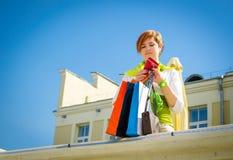 Giovane bella donna con le borse dopo la compera fotografia stock