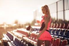 Giovane bella donna con le cuffie che posano sopra i sedili di scarica della spiaggia Vista posteriore Fotografie Stock
