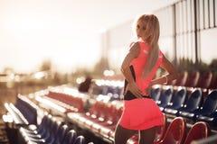 Giovane bella donna con le cuffie che posano sopra i sedili di scarica della spiaggia Vista posteriore Immagini Stock