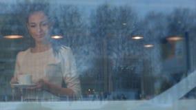Giovane bella donna con una tazza che cammina alla sua tavola in un caffè Fotografia Stock