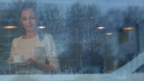 Giovane bella donna con una tazza che cammina alla sua tavola in un caffè Fotografie Stock Libere da Diritti
