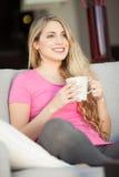 Giovane bella donna con una tazza sul sofà Immagine Stock