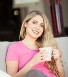 Giovane bella donna con una tazza sul sofà Fotografia Stock