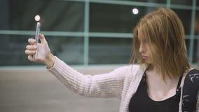 Giovane bella donna dai capelli rossi che fa selfie sul suo smartphone all'aperto alla notte Fondo della città di notte Movimento stock footage