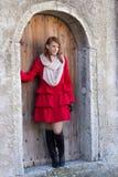 Giovane bella donna dai capelli rossi che posa davanti alla vecchia porta Fotografia Stock