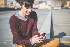 Giovane bella donna dei pantaloni a vita bassa che per mezzo dello Smart Phone Fotografie Stock Libere da Diritti