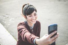 Giovane bella donna dei pantaloni a vita bassa che per mezzo dello Smart Phone Immagine Stock Libera da Diritti